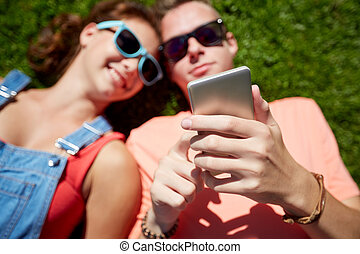 teenage couple with smartphone lying on grass - love and...