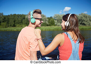 teenage couple with headphones on river berth - holidays,...
