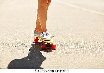 legs of young woman riding skateboard on road