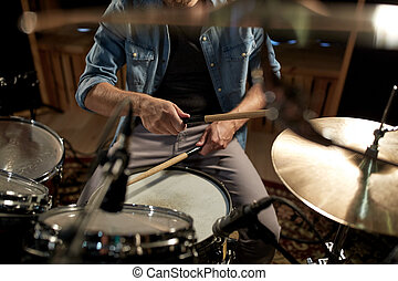 male musician playing drums and cymbals at studio - music,...