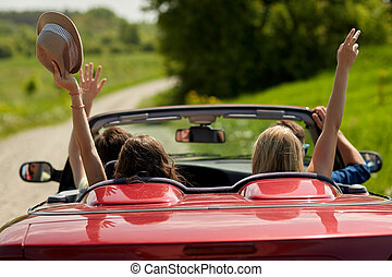 happy friends driving in cabriolet car at country - leisure,...