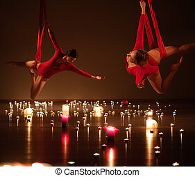 Two young girls in red performing aerial yoga in relaxing...