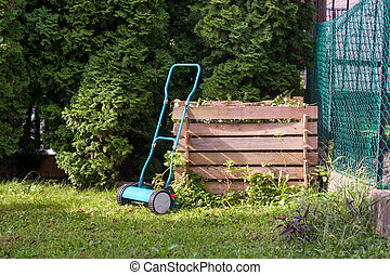 Manual lawn mower at a wooden compost bin