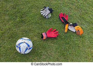 soccer gloves and ball on grassy field - dirty and used...