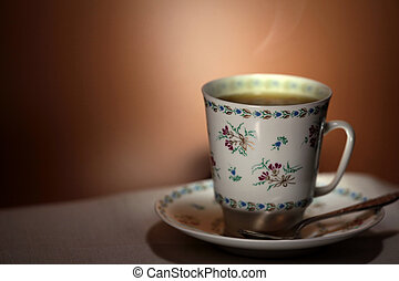 cup with hot tea and steam on background