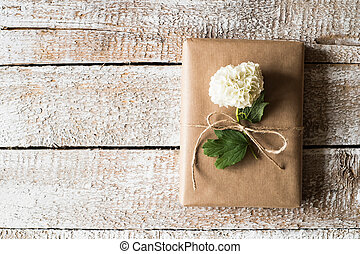 Present wrapped in brown paper, lilac flower laid on it. Studio