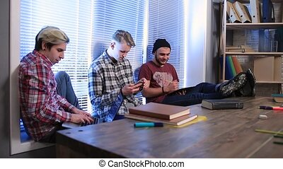 Group of students studying using digital devices - Young...