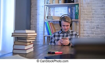 Smiling hipster using smartphone to listen music - Happy...
