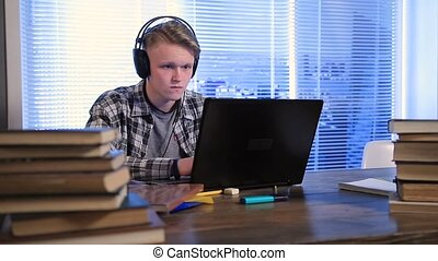 Serious student e-learning online with laptop - Handsome...