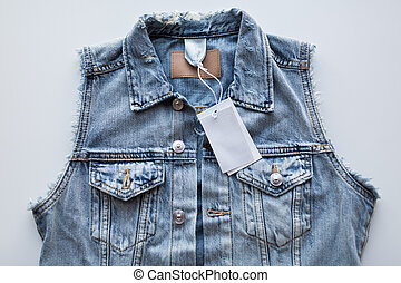 close up of denim waistcoat with price tag - clothes, wear...