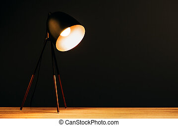 Desk lamp on table in dark office with copy space