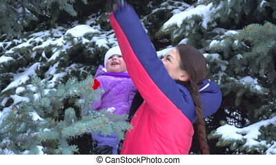 girl holding in her arms a child and shakes off the snow...
