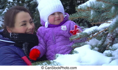 mother with little girl shake the snow from christmas trees