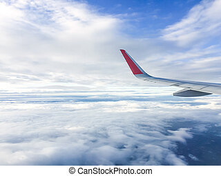 Wing of airplane flying above the clouds in the sky, looking...