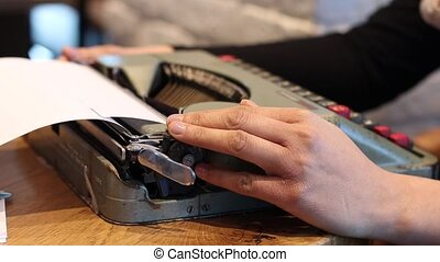 Close up on woman using typing machine - Loading a4 page...