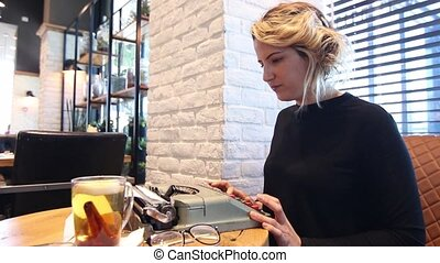 Woman with typewriter in a cafe - Woman using typing machine...