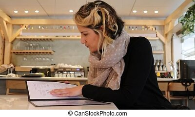 Woman search for options on menu in a restaurant - Woman...