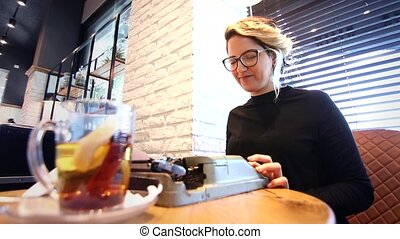 Sophisticated looking writer with typewriter - Blogger using...