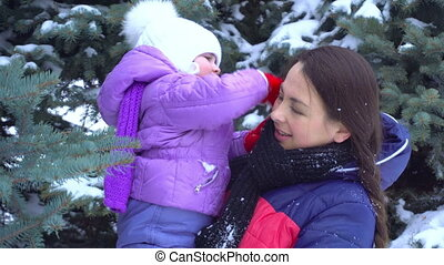 the child in the arms of mom shakes off the snow from her...