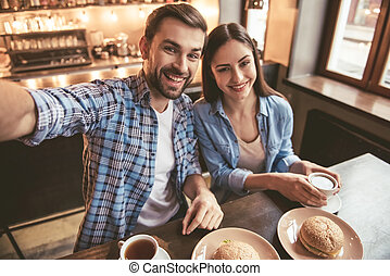 Couple at the cafe - Happy young couple is doing selfie,...