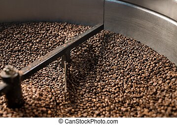 Coffee beans sifted and stirred in roasting machine -...