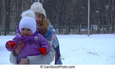 a young girl in a winter cap keeps the child in your arms