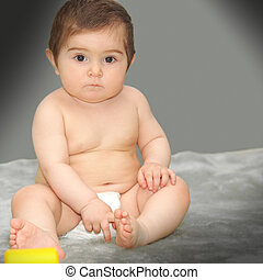 Serene baby sitting on gray carpet looking to camera