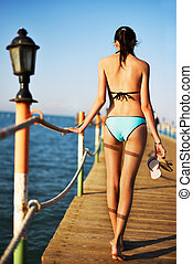 young woman going on a bridge in the sea, back view