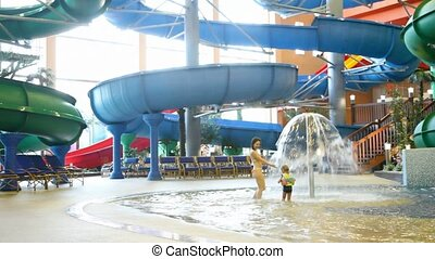 charming woman and girl run under fountain in indoor water park