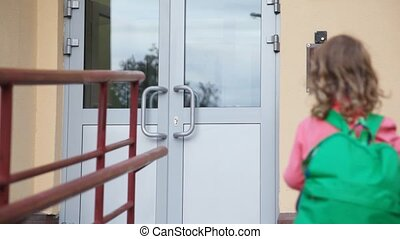 girl comes to door of housing and use entrance door intercom...