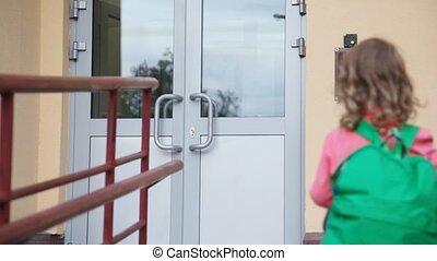 girl comes to door of housing and use entrance door intercom...