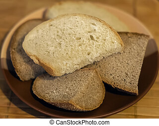 Pieces of white and black bread on a plate - The pieces of...