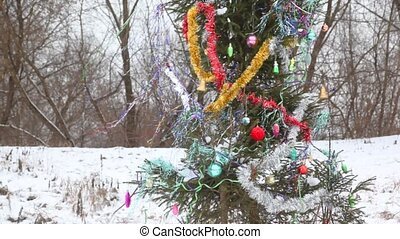 Decorated Christmas tree outdoor during snowfall - decorated...