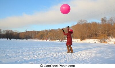 woman plays with air-balloon in wintry snowfield
