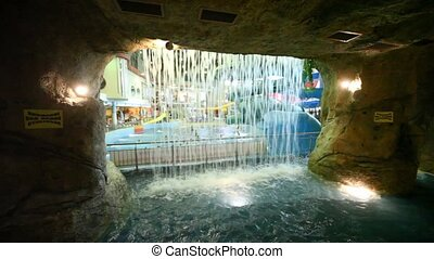Through a waterfall of stone cave seen people bathing in pool in waterpark
