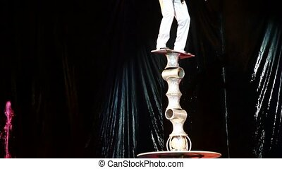 acrobat trys to keep balance while standing on tower of cylinders in circus