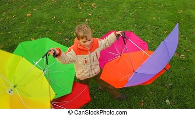 boy rotates with six umbrellas against grass - boy rotates...