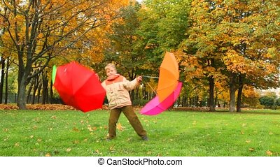 boy rotates with four umbrellas in autumn park