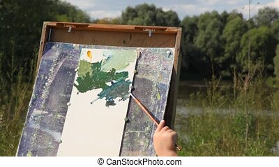 hands of adult man and girl painting landscape - hands of...