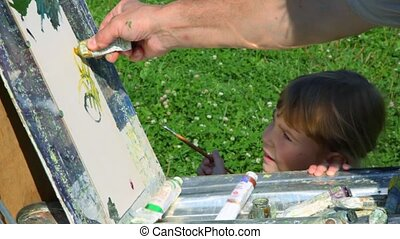 father teaching daughter to painting by oil paint in park