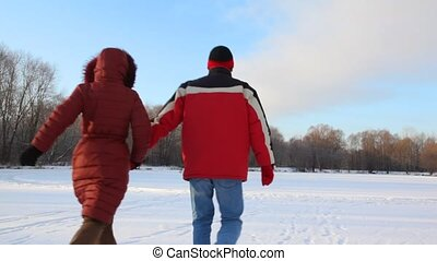 couple runs on snowfield from camera - couple having joined...