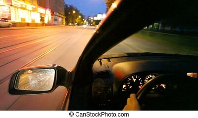 car driving on night city street with railroad, view on...