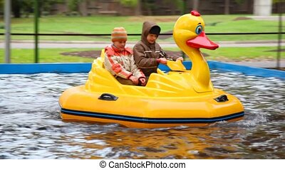 Boys riding duck-boat on water in amusement park - two boys...