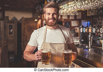 Handsome bearded bartender in apron is holding beer, looking...