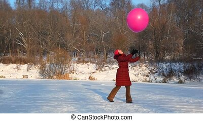 smiling woman throws up air-balloon in snowfield - young...