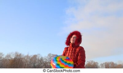 happy woman throws up balloon, winter