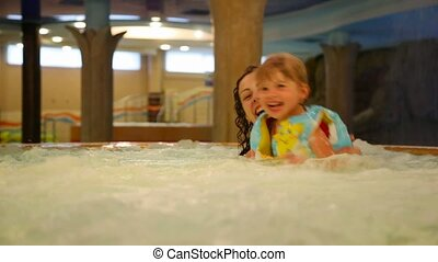 Woman and children bathe in a jacuzzi in water park - Woman...