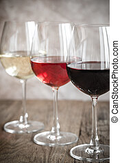 Glasses of red, rose and white wine on the wooden background