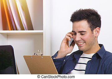 man smiling speaking by phone mobile by referring to the...