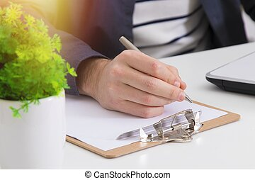 closeup of hand with pen writing or signing the document